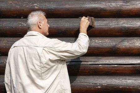 A house-painter cleans the brush the wall before painting