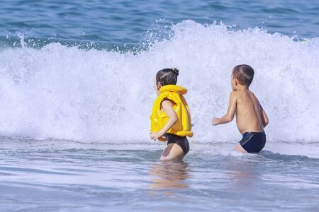 A little girl and a little boy are waiting for a big wave to jump on this wave.