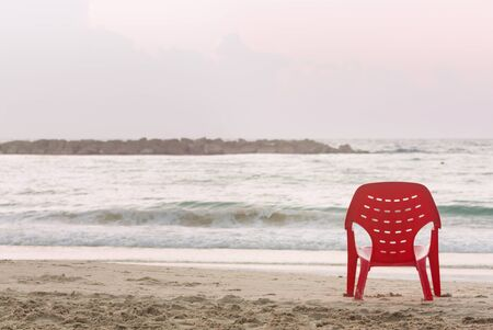 A red plastic chair stands at the waters edge on a sandy beach
