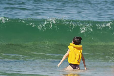 A little girl in a yellow life jacket stands in front of a big wave 写真素材