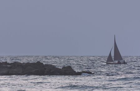 Seascape with sailing boat at dusk as background