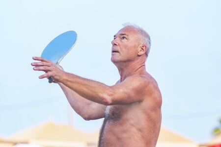 Adult male playing matkot on the beach Stockfoto