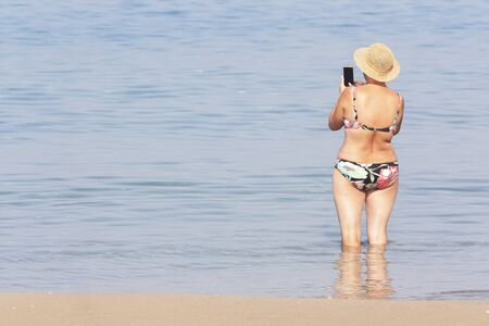 A woman in a swimsuit takes pictures of the sea on a smartphone