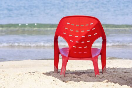 Resort background with red chair at the waters edge Stock Photo