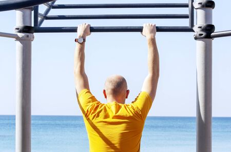 Guy on the horizontal bar on the beach sport ground with his back to viewer