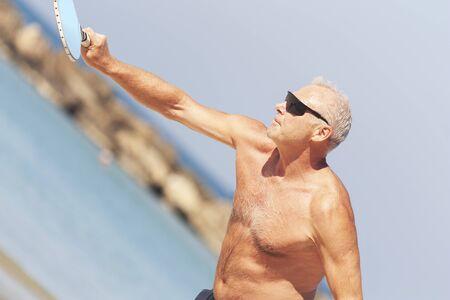 Adult male playing matkot on the beach Zdjęcie Seryjne