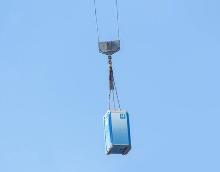 Moving a blue porta-potty through the air Standard-Bild