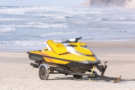 On a sandy beach by the sea there is a trailer with a yellow jet ski.