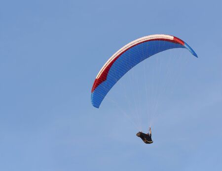 Paraglider is flying against the blue sky