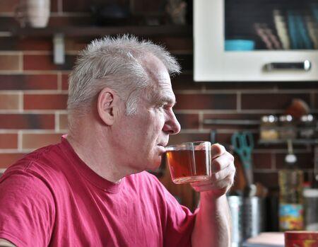 A man drinks tea in the kitchen Foto de archivo