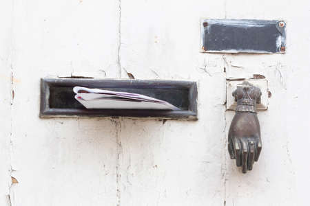 A bronze mailbox a name plate and a knocker on an old white door