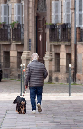 A man is walking his dog in the early morning when the whole city is still asleep