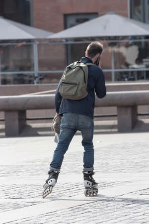 The guy moves around the city on roller skates talking on the phone as a concept of a mobile office