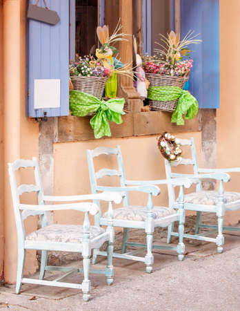 A window with open shutters decorated with Easter bunnies and baskets and antique chairs against the wall of an antique shop Zdjęcie Seryjne