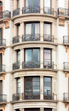 Facade of the house with round balconies and ionic pilasters