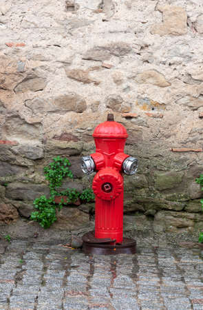 Red fire hydrant at the wall of a stone house