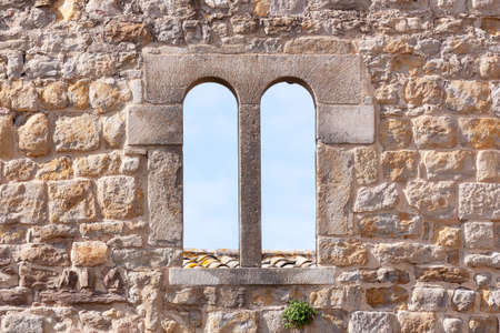 Arched viewing window in the stone wall of the old fortress