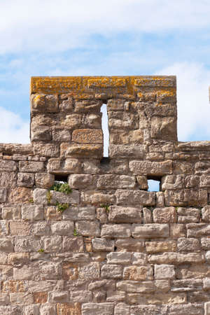 A narrow viewing hole in the stone wall of a medieval fortress