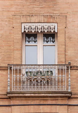 The wall of a brick house with a window and a cast iron balcony