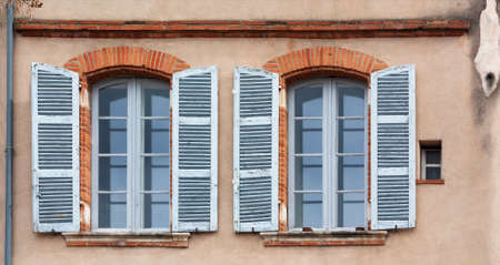 Windows with blue shutters on the wall of an old house