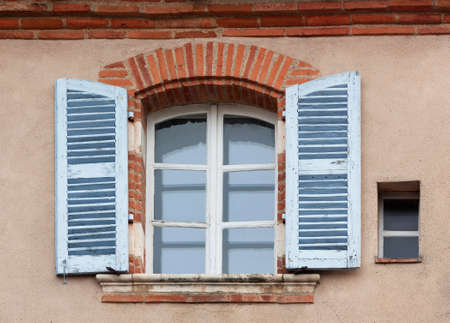 Window with blue shutters on the wall of an old house