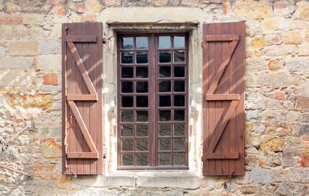 Windows with wooden shutters on the wall of a medieval stone house