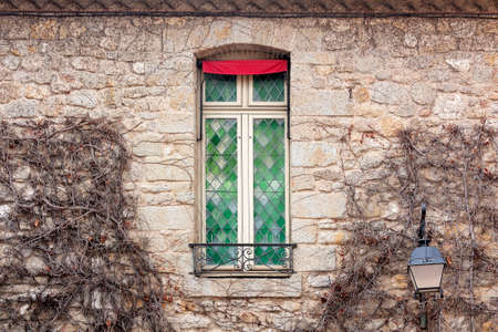 A stained glass french window on the wall of a stone house wrapped in ivy
