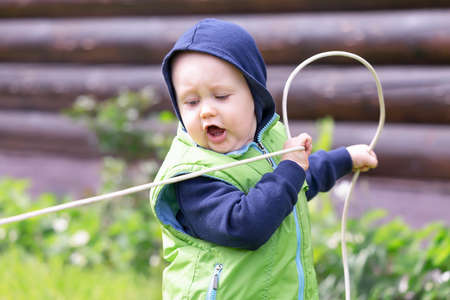 A toddler dressed in a vest and hoodie with an electric wire in his hands plays electrician in the rural Zdjęcie Seryjne
