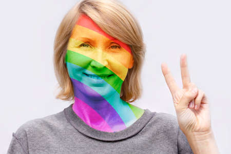 A woman wearing an inside out t shirt with her face painted in the colors of the rainbow shows a victory gesture in support of sexual minorities