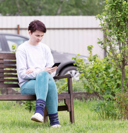 A girl in home clothes with a smartphone in her hand is sitting on a wooden bench