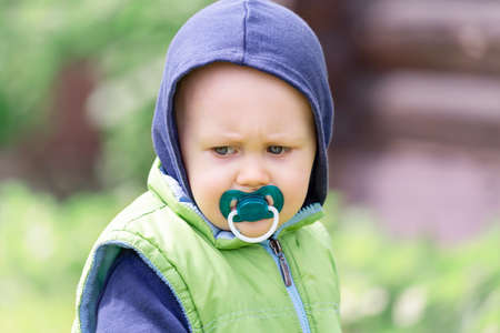 Portrait of an angry baby with a pacifier in his mouth on a green background Zdjęcie Seryjne