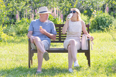 Curiously scene in the park with a man eating ice cream and a woman drinking beer