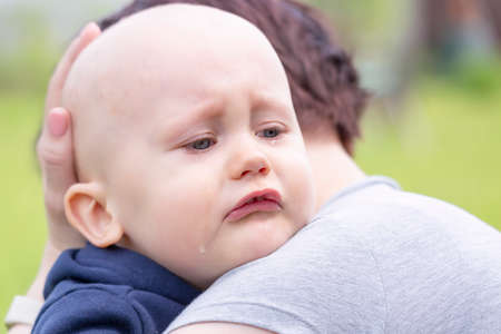 A mother comforts her crying little boy by holding him close and stroking his head