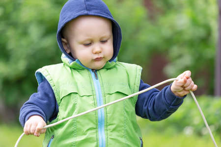 A toddler dressed in a vest and hoodie with an electric wire in his hands plays an electrician in nature