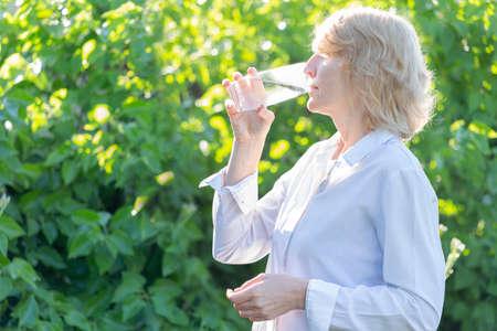 A woman takes a pill against a background of greenery Zdjęcie Seryjne