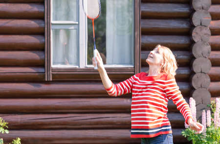 A woman plays badminton in front of a village house on a sunny day Zdjęcie Seryjne