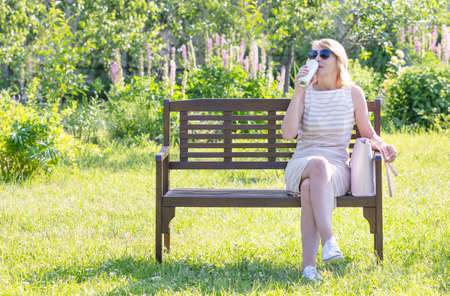 A woman drinks beer on a park bench