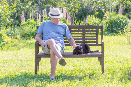 An unshaven man sits on a park bench with a cat
