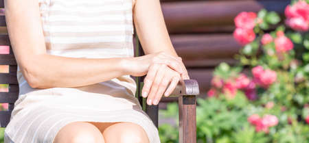 Hands of a middle aged woman sitting on a garden bench