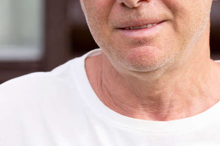 The chin of an unshaven smiling man
