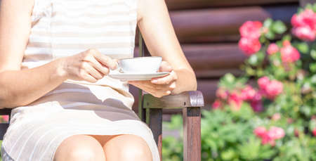 An elegant middle aged woman sits on a garden bench with a porcelain Cup in her hand
