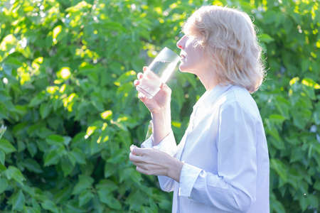 A woman takes a pill washed down with water from a glass in the early morning against a background of greenery Zdjęcie Seryjne
