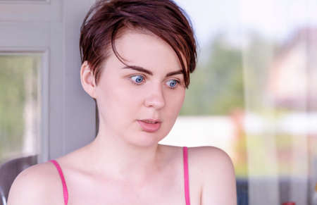 A blue eyed brunette with wide eyebrows and short hair looks down in fear