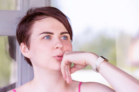 A blue-eyed brunette with short hair and wide dark eyebrows rests her cheek on her hand and talks thoughtfully about something sublime