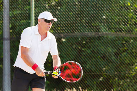 Close-up of an elderly tennis player playing tennis on an outdoor court