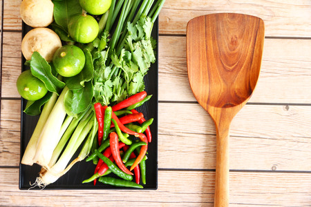 bush pepper: Thai Tom Yam soup herbs and spices, consisting of lemongrass, Kaffir Lime leaves, Galangal, Lemon and Red Chilli on an old wooden table.