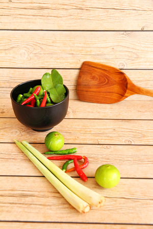 southeast asian ethnicity: Thai Tom Yam soup herbs and spices, consisting of lemongrass, Kaffir Lime leaves, Galangal, Lemon and Red Chilli on an old wooden table.