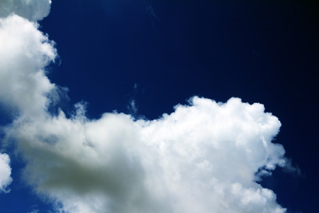 wisps: Hazy blue summer sky background with wisps of fine cirrus clouds in an empty expanse of cerulean blue for a fresh tranquil nature abstract. Stock Photo