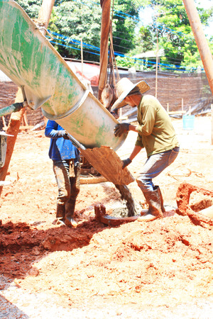 concrete truck: A construction worker works with a concrete truck and spreads concrete around to create a slab for the floor of a new building.