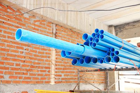 pipework: Stacked blue PVC plumbing tubes.